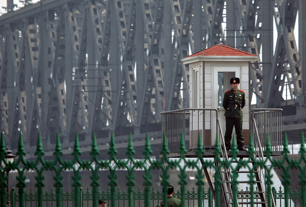 This picture taken on April 6, 2013 shows a Chinese border guard standing on a look out post by the bridge that crosses the Yalu river to the North Korean town of Sinuiju across from the city of Dandong. The US is pressuring China's new President Xi Jinping to crack down on the regime in North Korea or face an increased US military presence in the region, The New York Times reported late April 5, 2013. CHINA OUT AFP PHOTO (Photo credit should read STR/AFP/Getty Images)